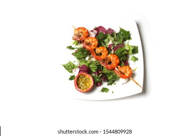 Grill Shrimps On Skewer On Fresh Green Salad On The Plate Isolated On White. Top View, Flat Lay.