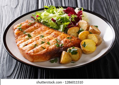 Grill steak swordfish served baby potato and fresh salad close-up on a plate on a black background. horizontal