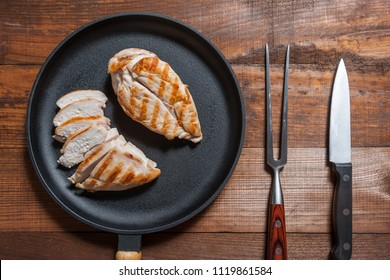 Grillad chiken fillet on pan, cooked meat. Wooden background, flat lay