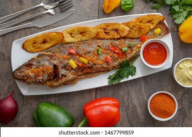 Grilled African Fish Dish. Smoked fish in Nigerian Meal. Fish Soup Cuisine. Plantains Dish Baked Fish African Meal