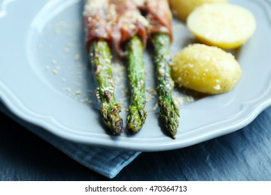 Grilled asparagus with bacon and potatoes on plate