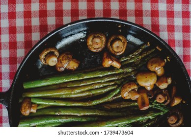 Grilled asparagus and mushrooms in a cast iron skillet, served on a red checkered tablecloth