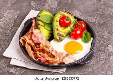 Grilled bacon and avocado, fried eggs with spinach and cherry tomatoes in cast-iron pan. Gray concrete background. Ketogenic diet. Low carb high fat breakfast. Healthy food concept