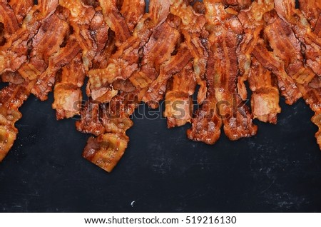 Grilled bacon on black background.
