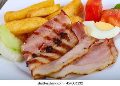Grilled bacon with potato, onion and tomato
