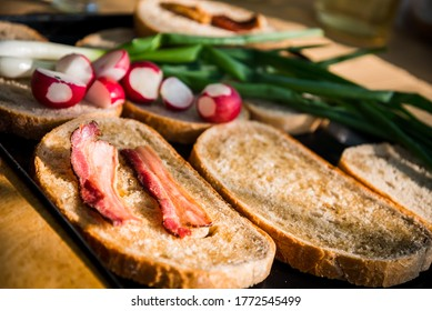Grilled bacon slice on fatty bread with green onion and fresh radish on a hungarian summer grill party. Barbeque background