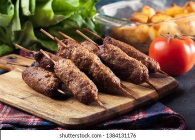 Grilled balkan cevapcici or shish kebab on skewers served on cutting board
