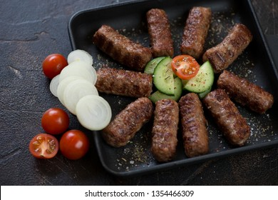Grilled balkan cevapi or cevapcici sausages in a cast-iron serving tray, close-up, studio shot