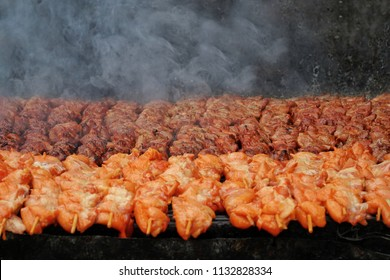 Grilled barbecue meat on skewers over fire with smoke cooking on a coal.Preparation of delicious appetizing giblet chickens roasted on hot grill.Food,Healthy,Picnic Concept.