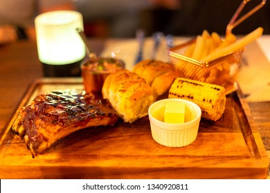 Grilled barbecue ribs pork with corn and  bread on wooden plate.
