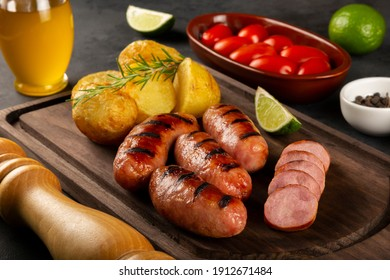 Grilled barbecue sausages on dark background.