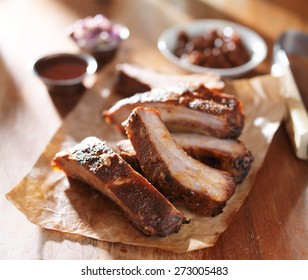 grilled barbecued spare ribs with baked beans and coleslaw  on wooden cutting board