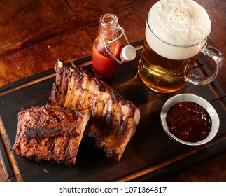Grilled or barbecued spicy ribs with a cold beer with frothy head served on a tray with chutney and tomato ketchup for a tasty finger snack pub lunch