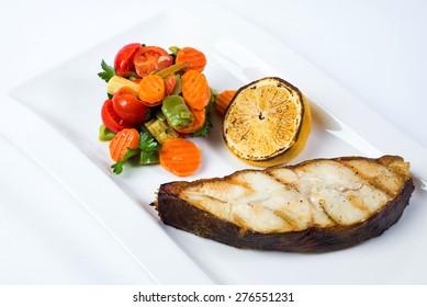 grilled barramundi steak with lemon and vegetables.