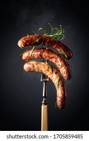 Grilled Bavarian sausages with rosemary. Sausages on a fork sprinkled with rosemary.