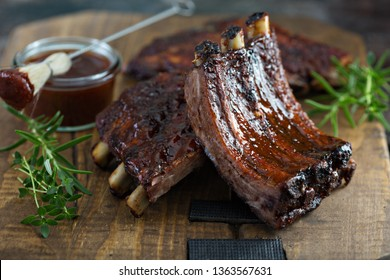 Grilled bbq ribs with barbeque sauce on a board