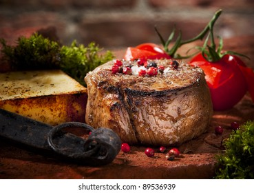 Grilled bbq steak with potato cube and tomatoes.