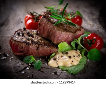 Grilled bbq steaks over wooden background
