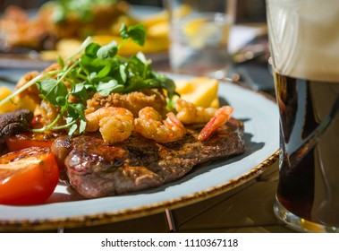 Grilled beaf steak meat served with roasted tomato, watercress, prawns and glass of beer.