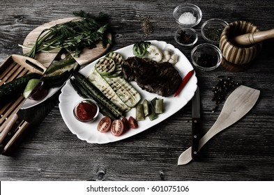 Grilled beef grilled with asparagus, zucchini, lobi, broccoli, tomato, chili and red sauce on a white plate, and other vegetables in wood background