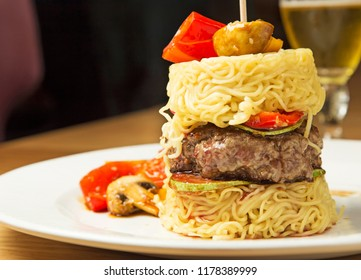 Grilled beef burger served in rice noodle stack with grilled vegetables and sesame seed