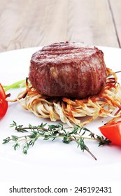 grilled beef fillet pieces on noodles with tomatoes dry spices and green thyme twigs on white plate over wood