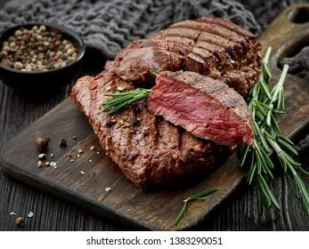 grilled beef fillet steak meat on dark wooden table