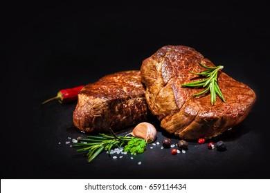 steaks de filet de boeuf grillé avec herbes et épices sur fond noir