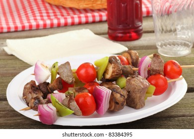 Grilled beef kabobs and various vegetables on a picnic plate