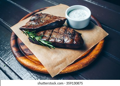 Grilled beef liver on the wooden plate.