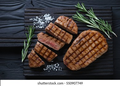 Grilled beef medallion steaks on a black wooden cutting board, flat-lay view