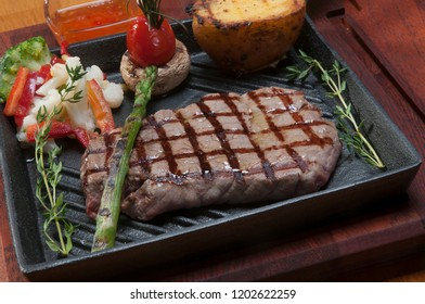 grilled beef on frying cast iron serving pan with vegetables and sauces. Red and mustard sauces in bowl. Serving pan is black and clear on wooden board.