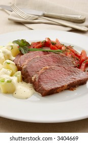 Grilled beef on white plate with potatoes salad and tomatoes