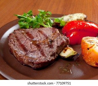 Grilled beef on white plate  with vegetable . Close-up