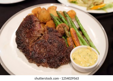 grilled beef ribeye steak on charcoal served with grilled vegetables, carrots, asparagus and mustard sauce