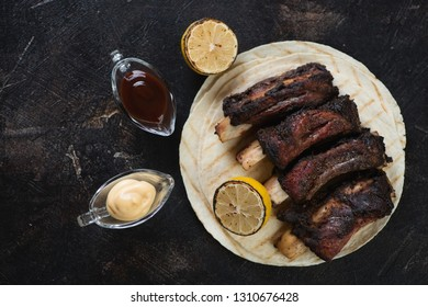 Grilled beef ribs with tortillas and dipping sauces on a dark brown stone background, flatlay, horizontal shot