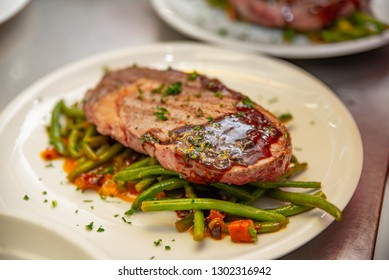 Grilled beef sirloin steak with grilled beans and bacon