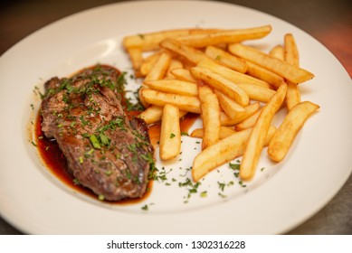 Grilled beef sirloin steak with fries and sauce