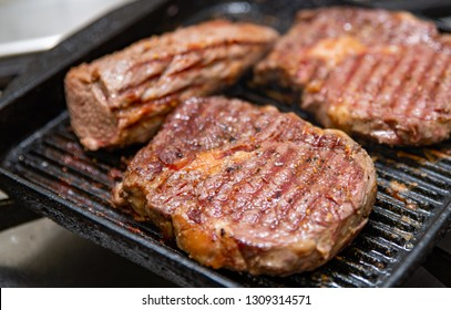 Grilled beef sirloin steak on grill