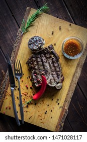 Grilled Beef Steak with Bourbon Sauce on wooden cutting board. Red chilli pepper and thyme on the brown wooden background. Vertical photo.