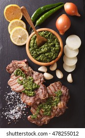 grilled beef steak with chimichurri sauce close-up on slate board. vertical view from above