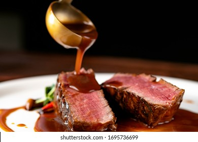 Grilled beef Steak filet Mignon medium rare pour demi-glace sauce