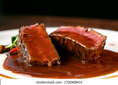 Grilled beef Steak filet Mignon medium rare pour demi-glace sauce