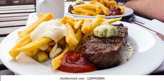 Grilled beef steak with French fries, mayonnaise, ketchup and herbal butter outside in beer garden on wooden table background