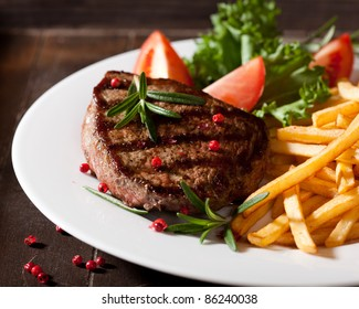 Grilled beef steak with french fries, tomatoes, lettuce and fresh rosemary. Home made food. Concept for a tasty and hearty meal.  Rustic wooden background. Close up.