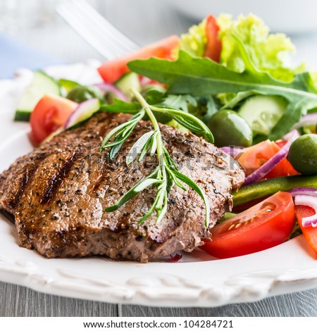 Grilled beef steak with green olives, lettuce, cucumber, lettuce and rocket. Concept for healthy nutrition. Close up.