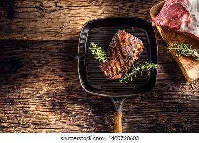 Grilled beef steak in grill pan with herbs rosemary on wooden table.