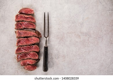 Grilled beef steak on black stone table. Top view with copy space