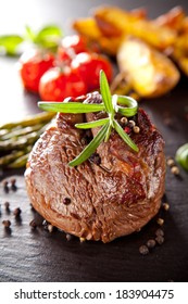 Grilled beef steak on black stone table with grilled vegetable