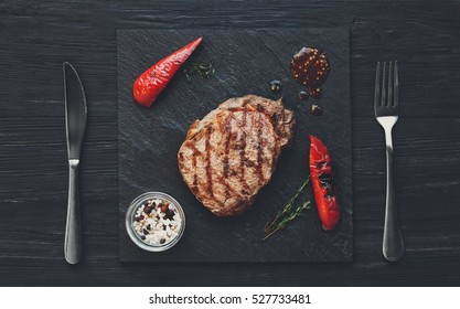 Grilled beef steak on dark wooden table background, top view. roasted on barbecue juicy red meat with rosemary, chili peppers and cutlery on stone board. restaurant food, filtered image